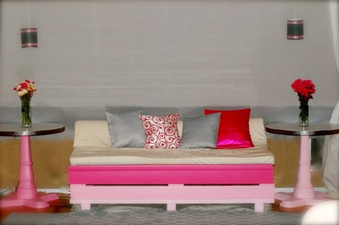 Idea mobili con bancali, divano per la cameretta in pallet di colore rosa con cuscini colorati