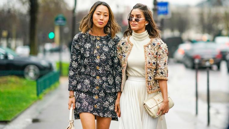 Due dine con vestiti eleganti, gonna bianca e giacca con decorazioni e occhiali da sole