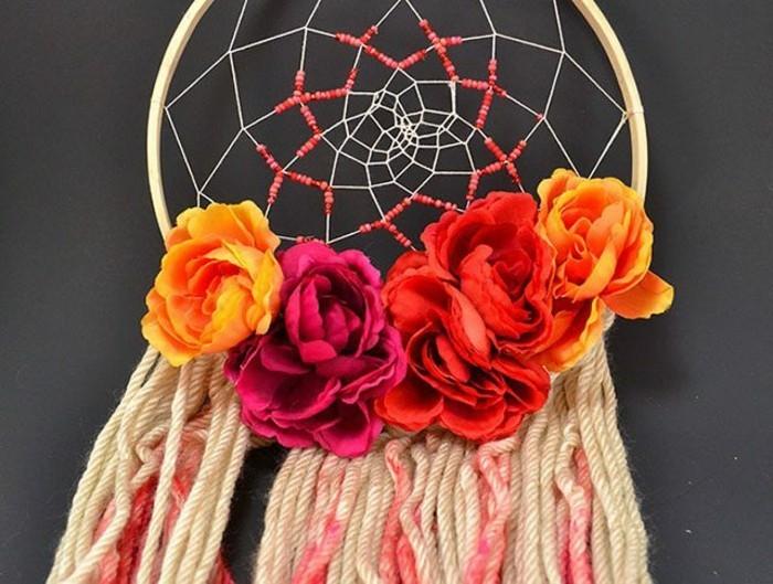 un modello di dream catcher caratterizzato da alcuni fiori colorati posti all'inizio delle frange
