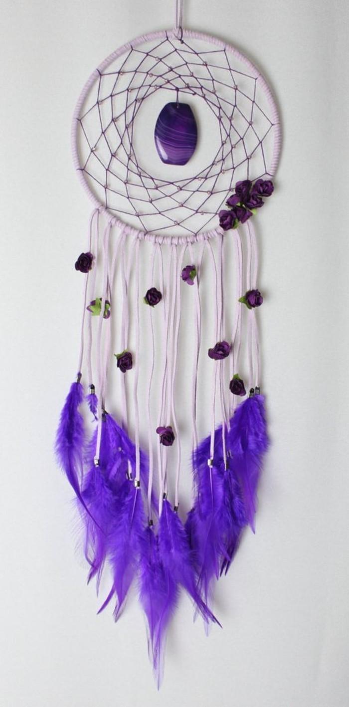 un modello di dream catcher da usare come un talismano, con pietre e piume viola