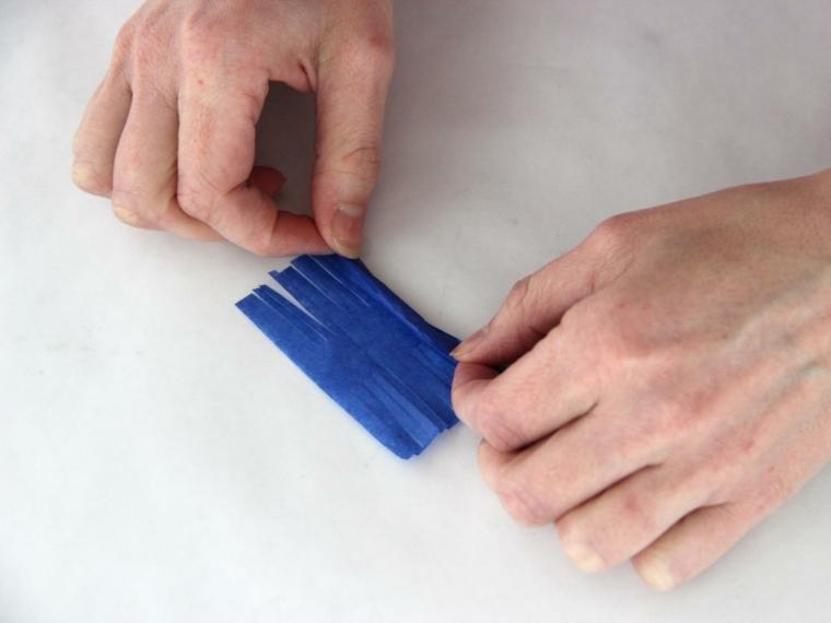 un passaggio per la creazione di decorazioni pasquali fai da te: piegare la carta crespa ritagliata
