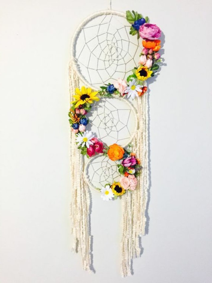 un modello particolare di acchiappa sogni con i cerchi e le frange bianchi e fiori colorati