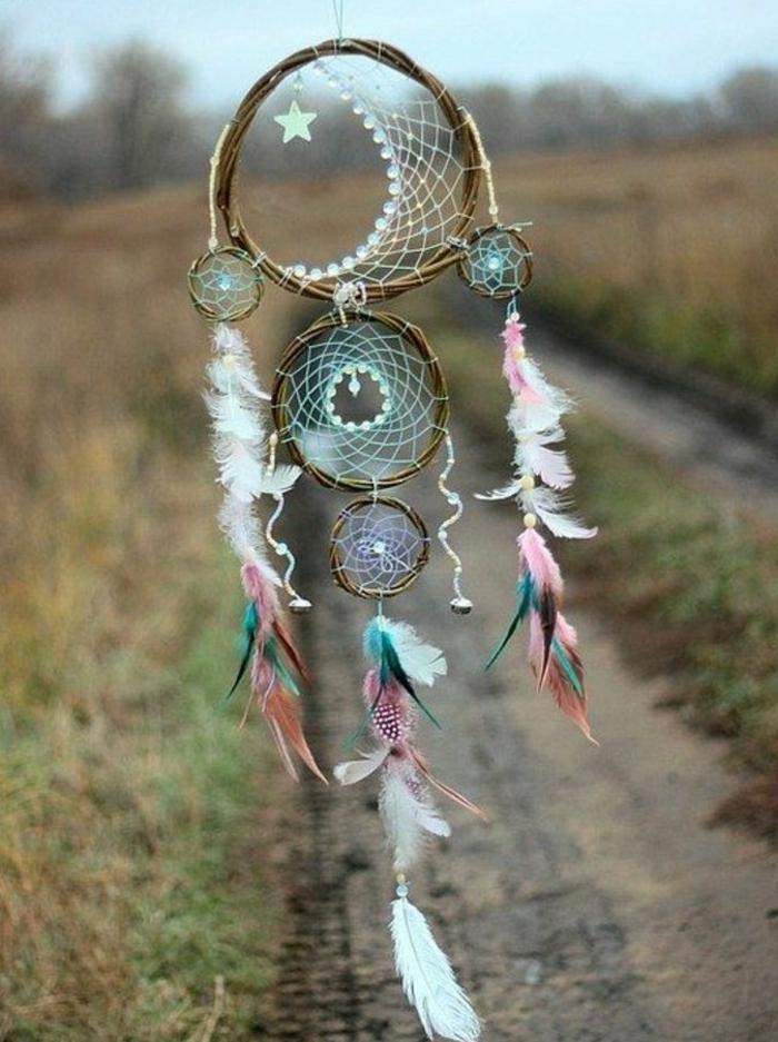 un modello particolare di dream catcher con un grande cerchio e quattro più piccoli, piume colorate, perline e una stella
