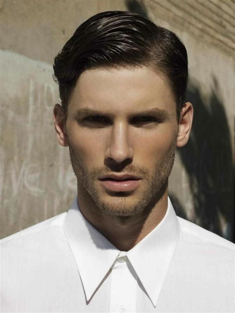 un modello che sfoggia un taglio capelli uomo corti, camicia bianca e barba incolta