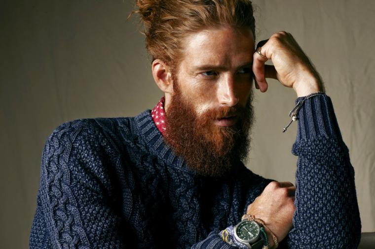 una proposta per tagli uomo di tendenza con man bun e barba lunga, maglione blu e camicia rossa