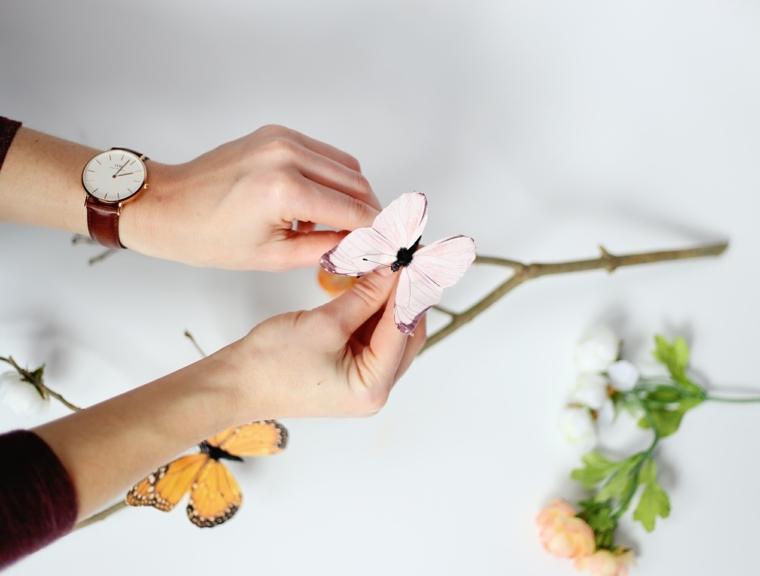 una fase dell'allestimento dell'albero di pasqua, l'applicazione di una farfalla al ramo