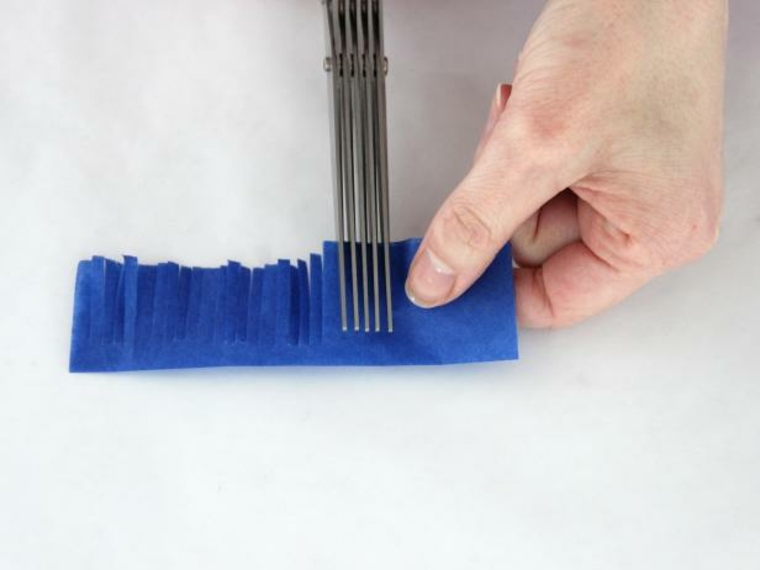 un passaggio per la creazione degli addobbi per l'albero di pasqua che prevede dei tagli con la forbice frangiata