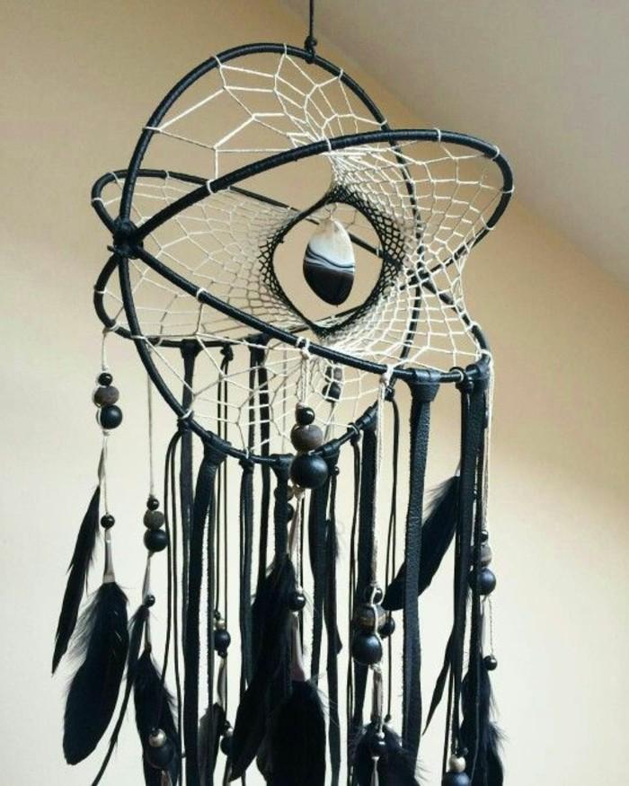 un modello di acchiappasogni con cerchi dalla forma originale, con delle piume nere come decorazione