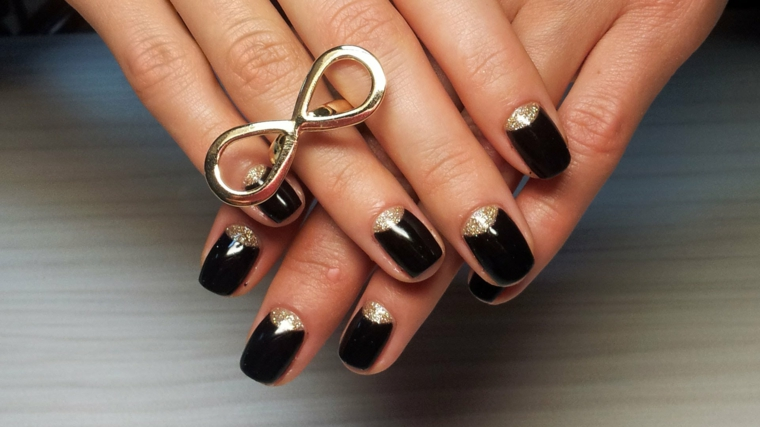 Unghie decorate con una french inversa di colore oro, anello infinito sul dito anulare