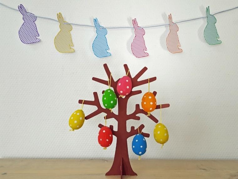 tanti coniglietti appesi ad un filo e un albero pasquale di cartone con appeso delle uova colorate a pois