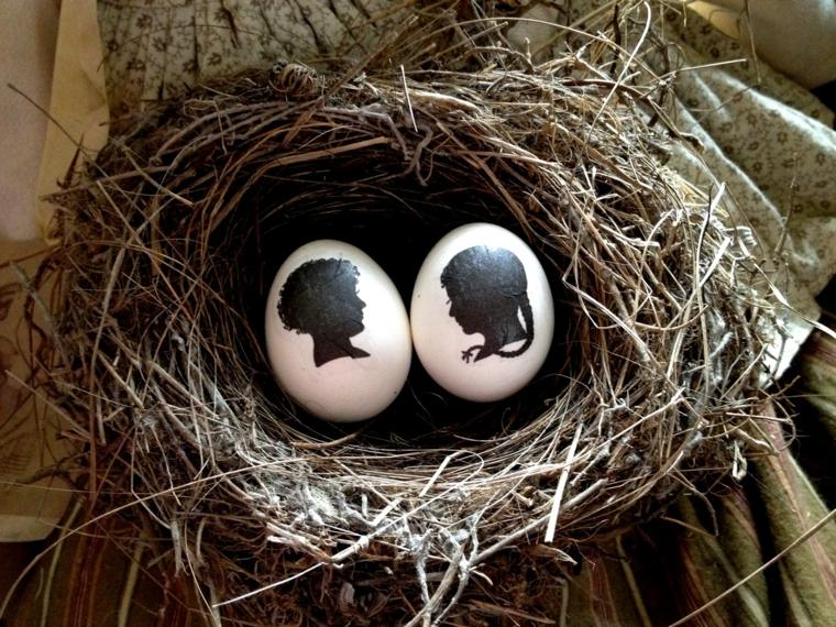 un'idea per come decorare uova di pasqua con dei profili neri di un uomo e di una donna
