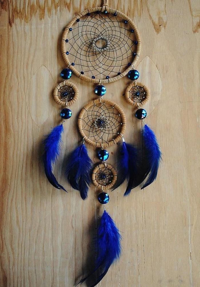 un bel modello di dream catcher con un grande anello e quattro più piccoli, piume e pietre blu