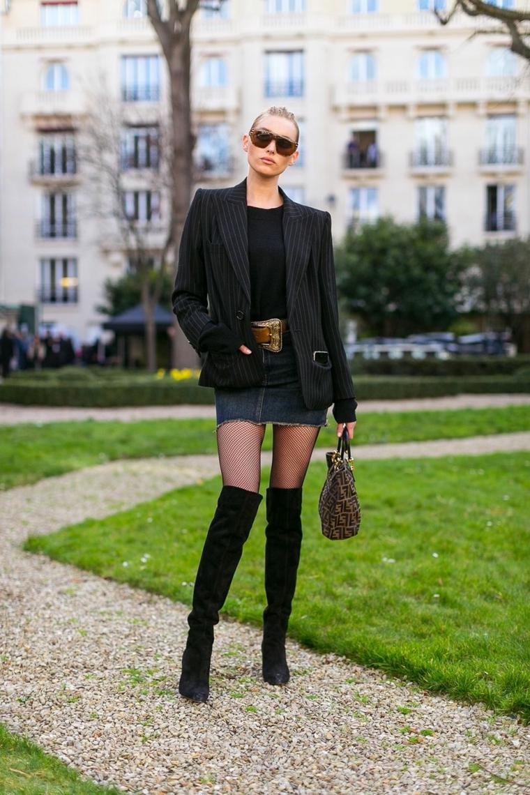 Donna con stivali molto alti e blazer nero in abbinamento, gonna in jeans con maglietta
