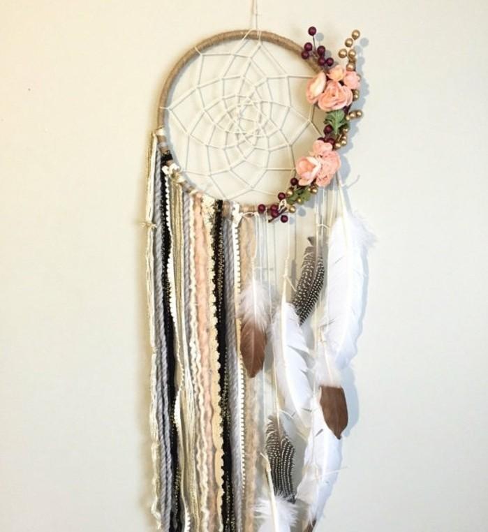 un modello di dream catcher realizzato con delle piume e delle strisce di tessuto e di pizzo, fiori e bacche sul cerchio