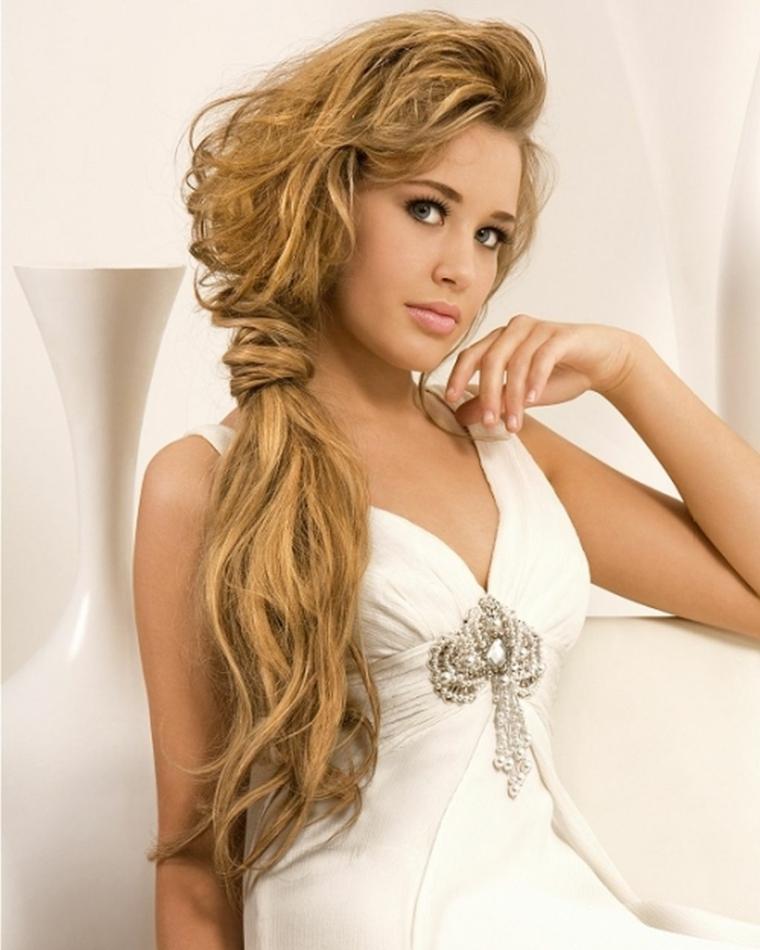 una proposta per acconciature capelli raccolti con una lunga coda a lato, abito bianco con dettaglio brillante al centro