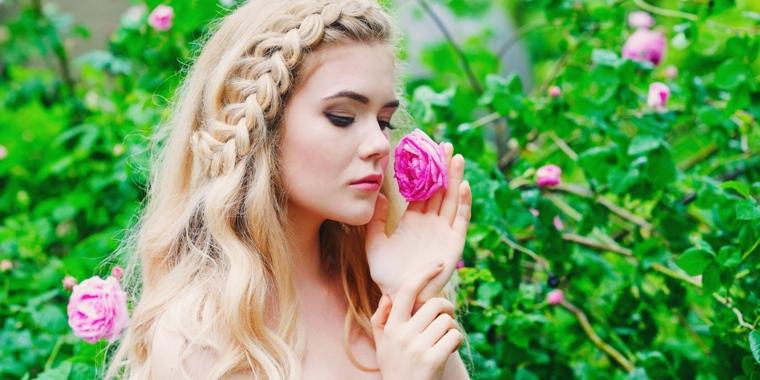 una proposta per acconciature capelli raccolti con una treccia laterale, una rosa tra le mani e alberi verdi come sfondo