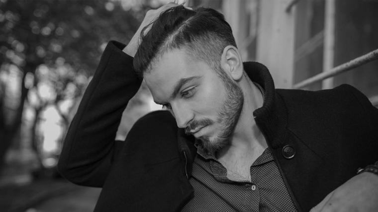 un esempio di tagli di capelli uomo corti ai lati, barba incolta, giacca e camicia