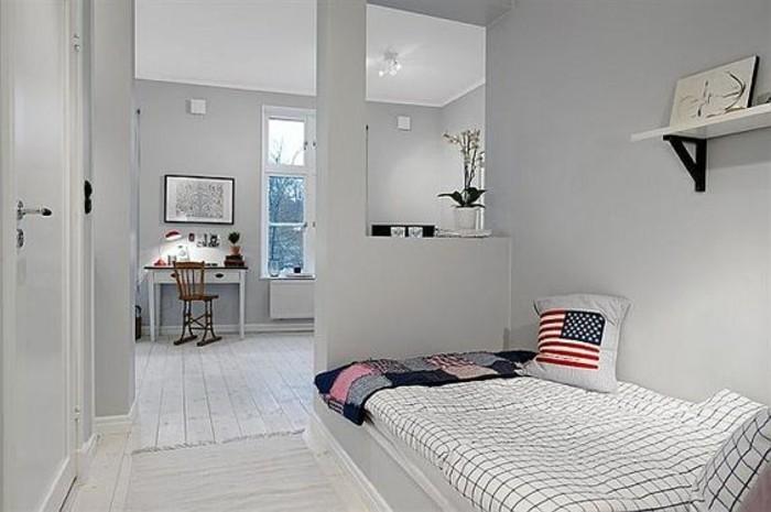 Zona note separata dal salotto con un piccolo muro divisorio con nicchia