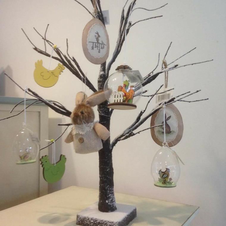un alberello finto con degli addobbi di stoffa a forma di pulcini e coniglietti e uova di vetro con all'interno dei pulcini