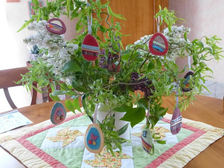 un centrotavola ad albero pasquale con degli addobbi in stoffa colorata a forma di uova