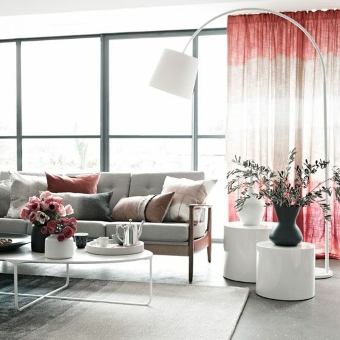 Salotto arredato con un divano e tavolini bassi di colore bianco, decorazioni floreali