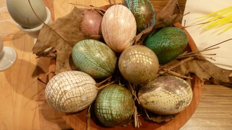 proposta per delle uova di pasqua decorare con dei motivi oro in un piatto di legno con delle foglie