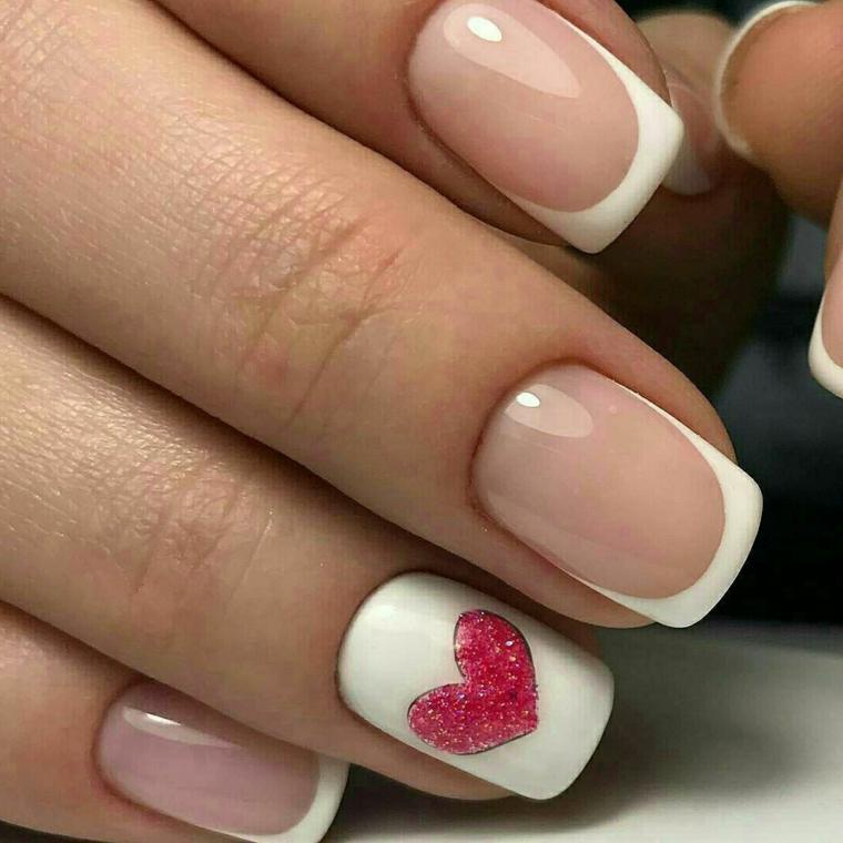 una proposta per unghie gel french con la particolarità dell'anulare bianco con un cuore rosso
