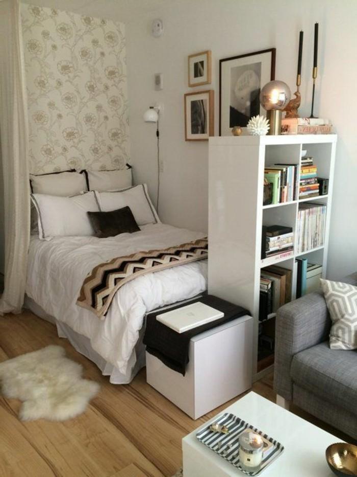 Arredare un open space con letto e divano di colore grigio, libreria come elemento divisorio