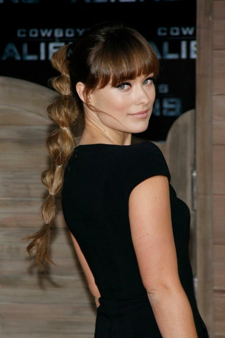 una ragazza con i capelli lunghi raccolti in una treccia particolare, maglia nera a maniche corte