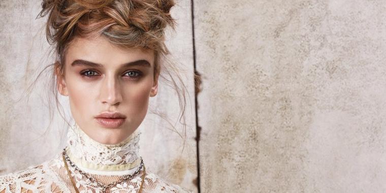 una proposta per capelli legati con una treccia sulla fronte e dei ciuffi morbidi a lato, rossetto marrone chiaro e collane