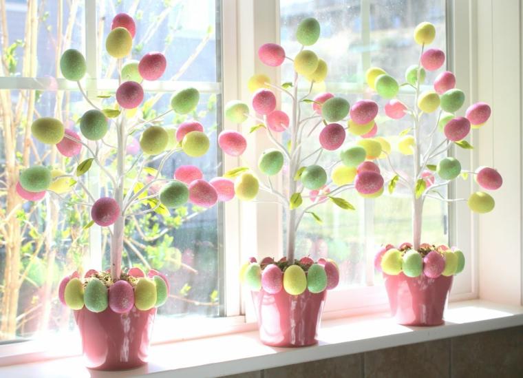 dei vasi rosa decorati con delle uova e dei rami bianchi con appese le uova colorate