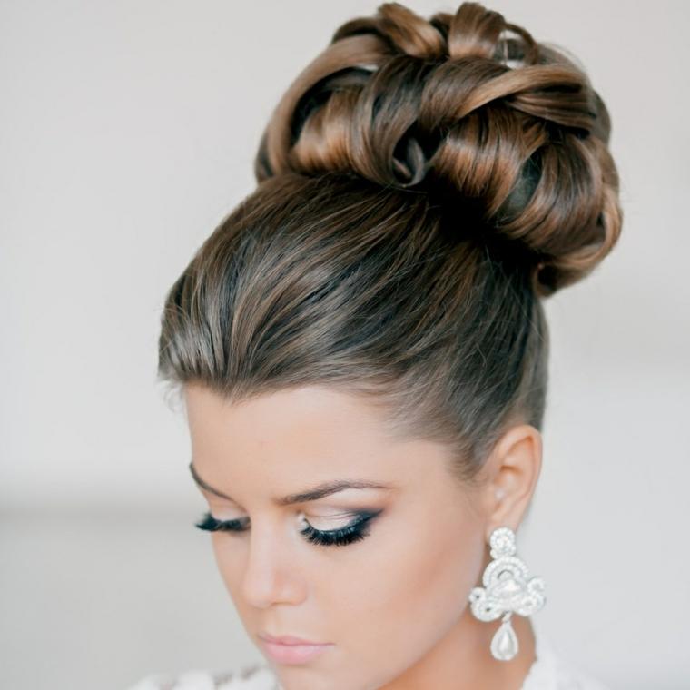 una ragazzo mostra un raccolto capelli ideali per una sposa elegante, orecchini grandi pendenti
