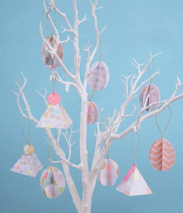 un albero con i rami bianchi addobbato per pasqua con uova e piramidi fai da te