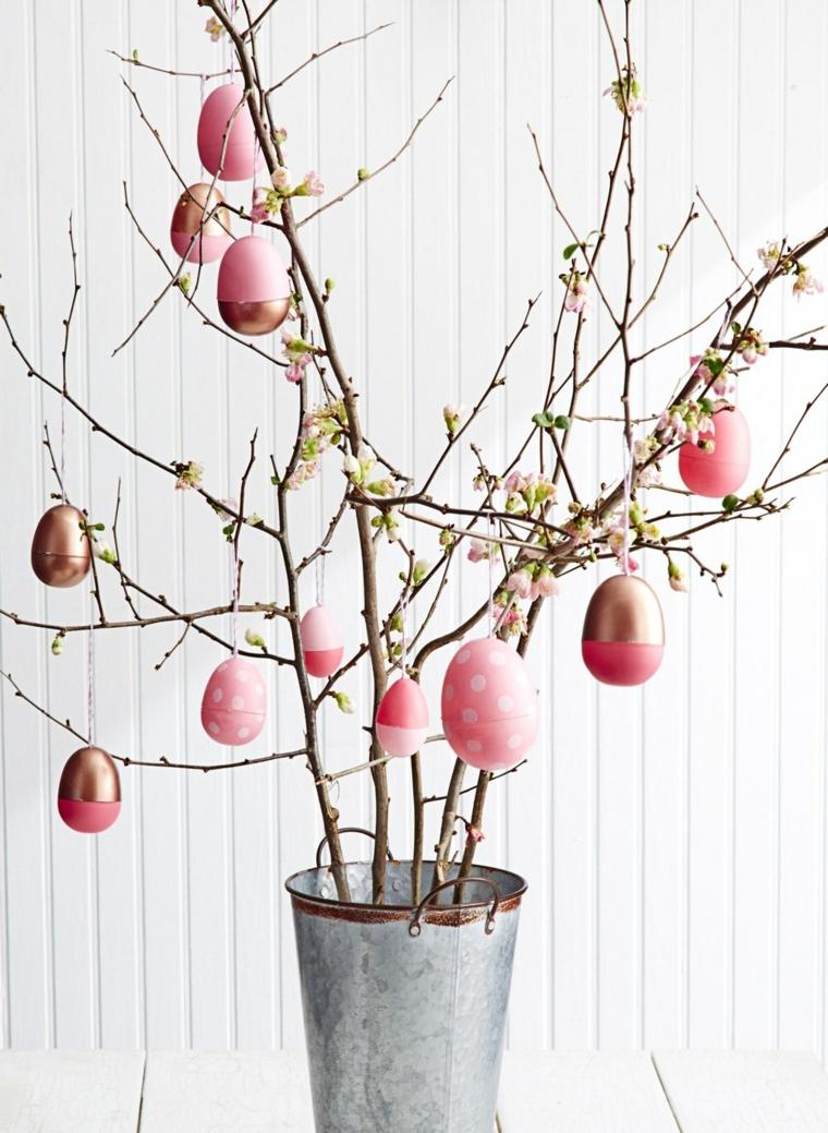una proposta per degli addobbi di pasqua fai da te creati con un secchiello, dei rami fioriti e delle uova decorate di rosa e oro