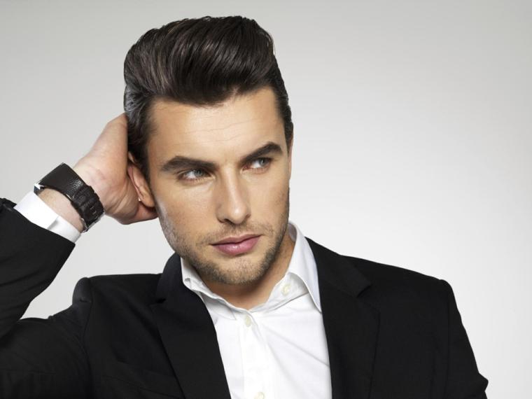 un modello con un taglio di capelli uomo con il ciuffo tirato all'indietro, orologio e vestiti eleganti