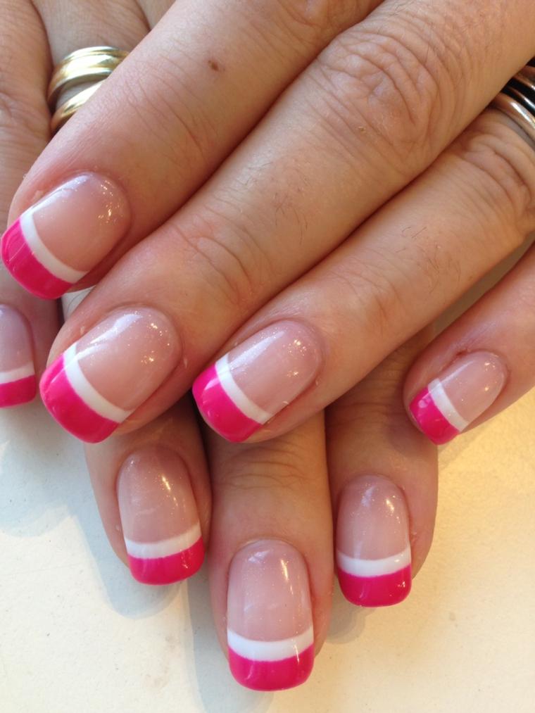 una proposta di manicure french colorato con smalto rosa ciliegia e riga bianca su base trasparente