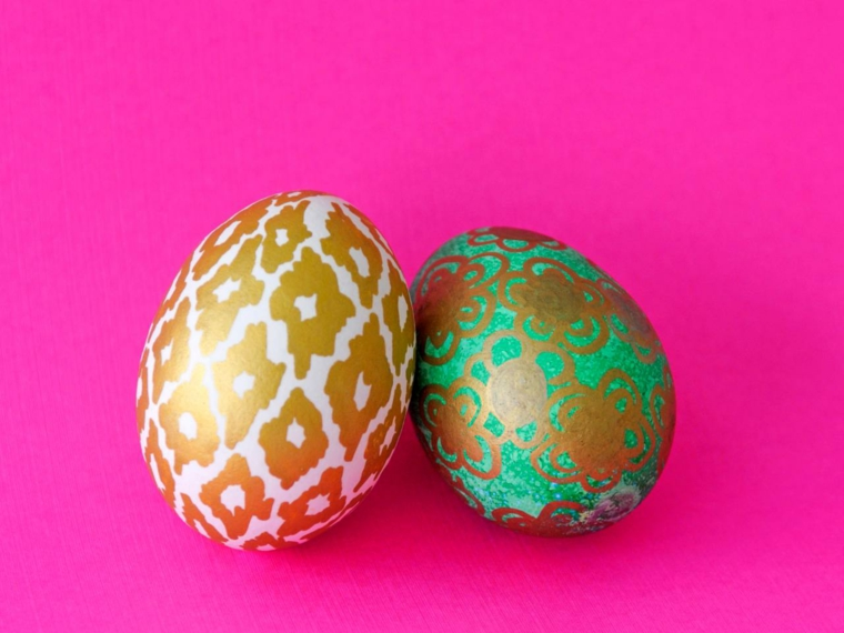 delle uova con delle decorazioni pasquali dorate su base bianca e verde, sfondo fucsia