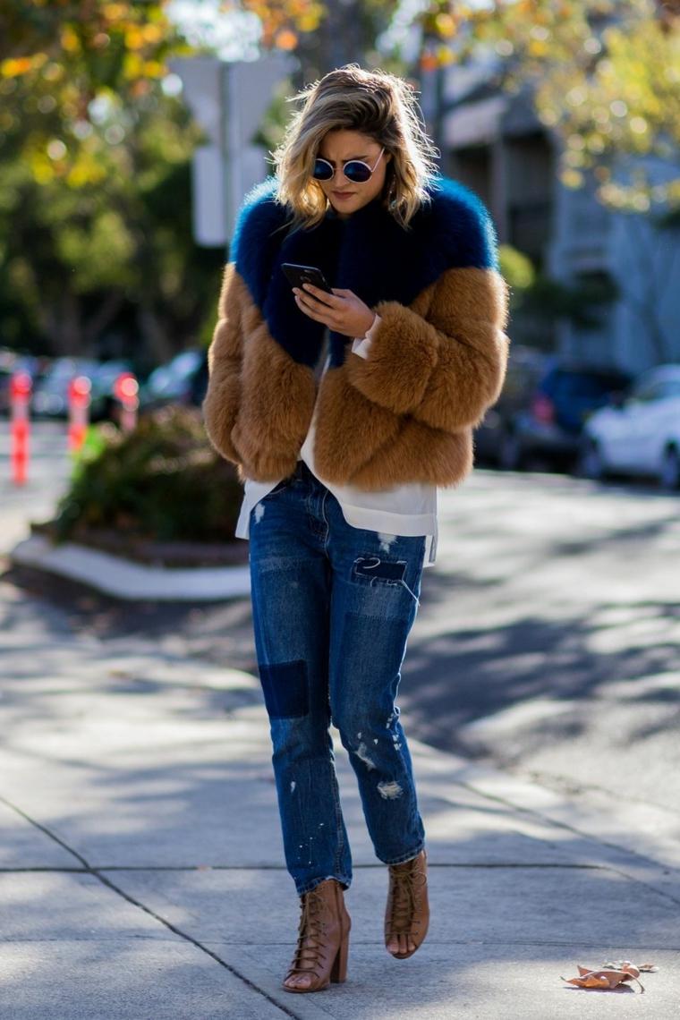 Jeans moderni con strappi in abbinamento ad una giacca colorata di pelliccia