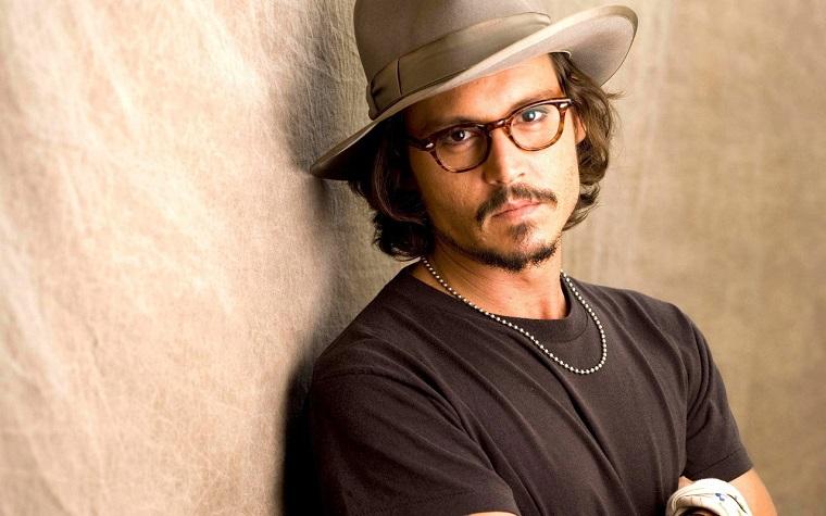 Uomini belli, stile casual per Johnny Depp, t-shirt nera in abbinamento al capello grigio e agli occhiali