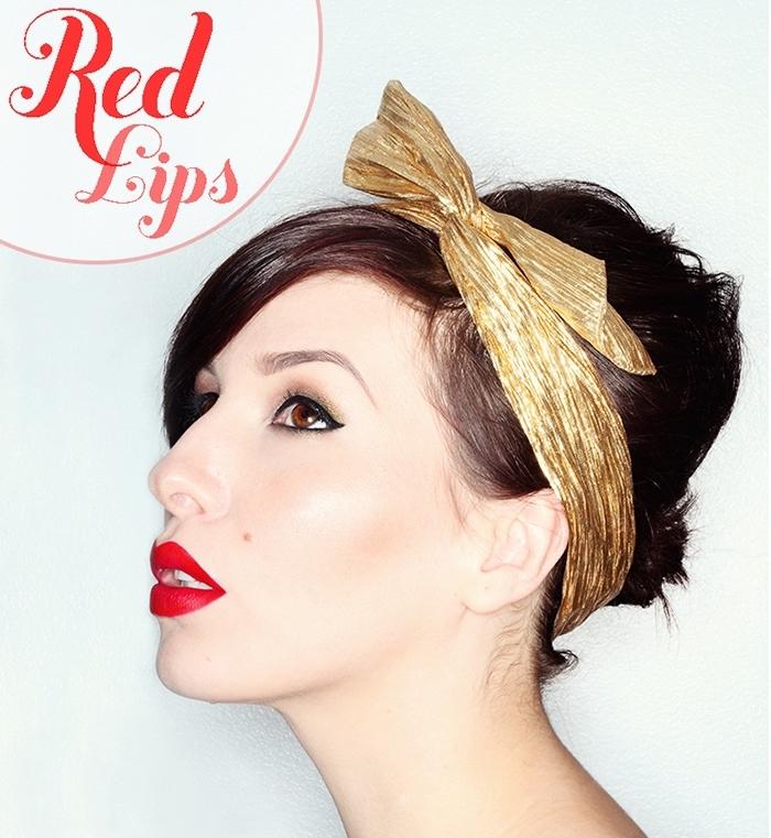 una ragazza con un'acconciatura raccolta con un grande fiocco dorato, labbra rosse ed eye liner nero