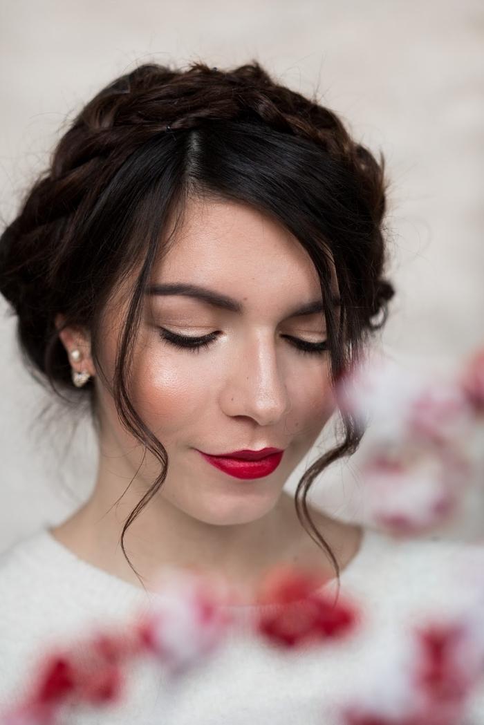 una ragazza con i capelli castano scuri raccolti, orecchini di perle bianche e labbra rosse