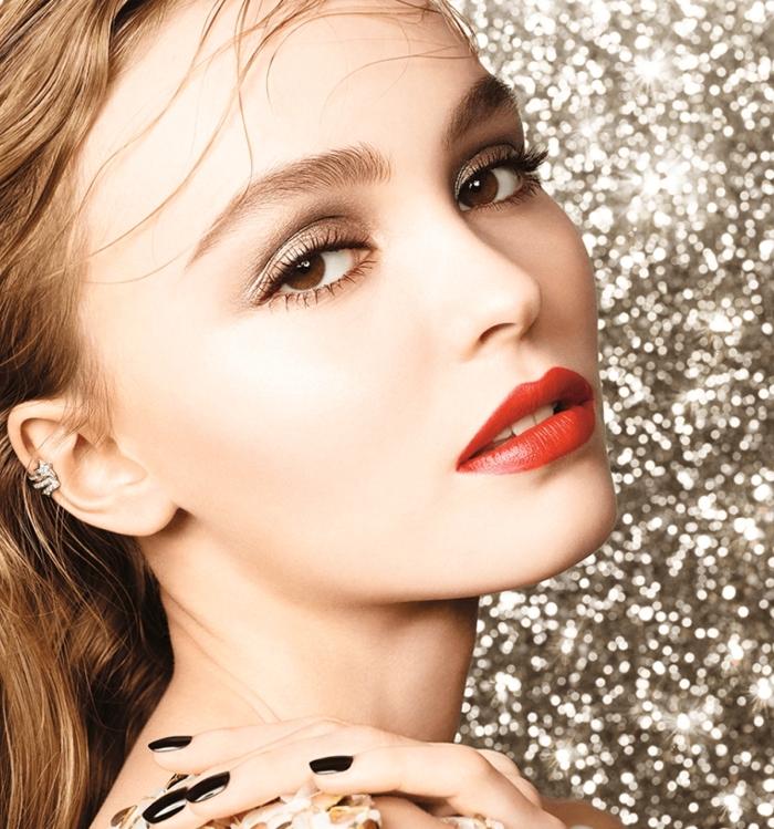 una ragazza con i capelli castano chiari e gli occhi color nocciola truccati con dell'ombretto marrone, unghie nere e rossetto rosso
