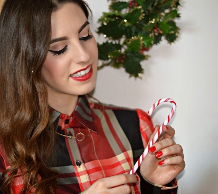una ragazza con i capelli lunghi castani, le labbra e le unghie rosse, una camicia rossa e nera e una caramella fra le mani
