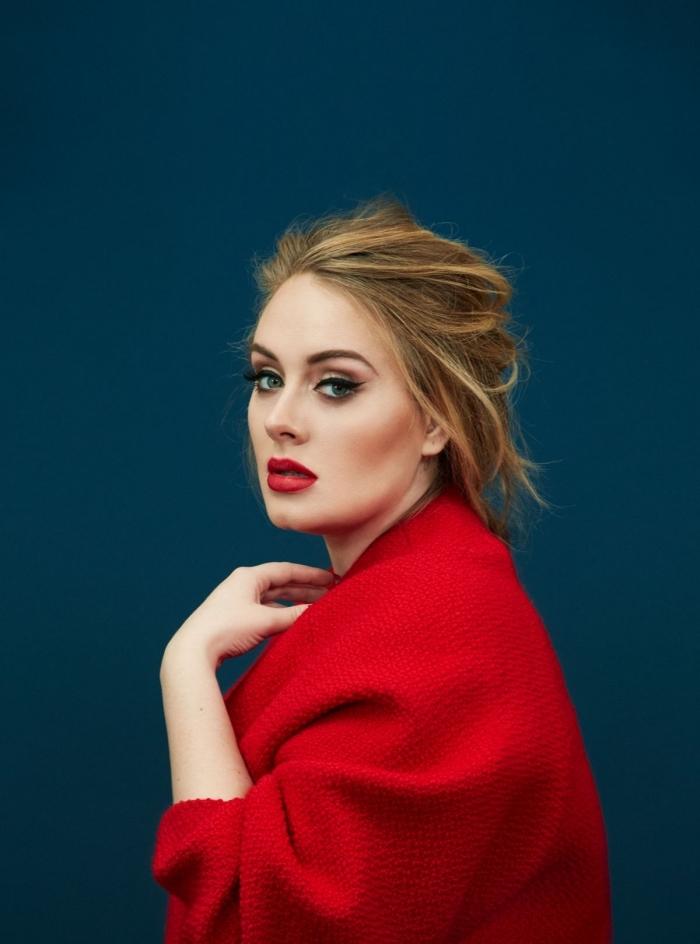 un makeup con le labbra rosse, gli occhi blu con dell'eye liner nero, un poncho rosso e i capelli raccolti morbidi