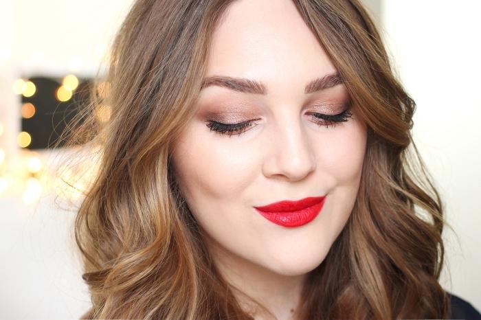 un makeup con rossetto di colore rosso scuro, gli occhi truccati con degli ombretti marroni