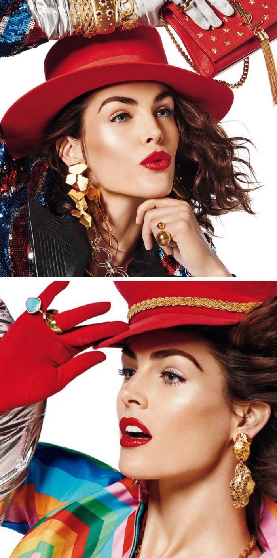 una ragazza con gli occhi blu truccati con dell'eye liner, rossetto rosso, cappello e guanti rossi