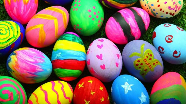 tante uova di pasqua decorate con colori vivaci e disegni come cuori, stelle, farfalle, spirali e righe