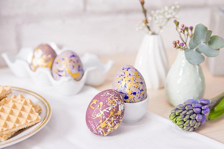 Uova colorate in modo originale, lavoretti di pasqua semplici, tavolo decorato con tovaglia bianca