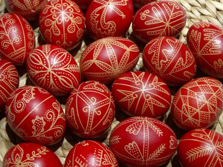 idea per come decorare le uova di pasqua con dei disegni dorati su fondo rosso scuro