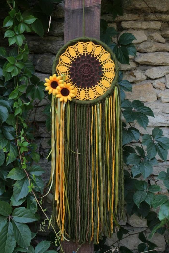 un bellissimo esemplare di dream catcher con dei girasoli come decorazioni e tela gialla e marrone